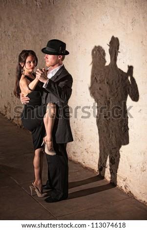 Beautiful female tango dancer with leg up next to partner - stock photo