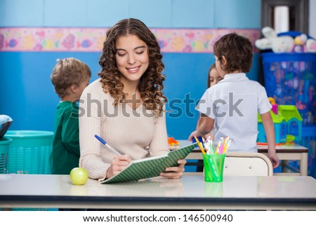 Beautiful female teacher writing in book with children in background at kindergarten - stock photo