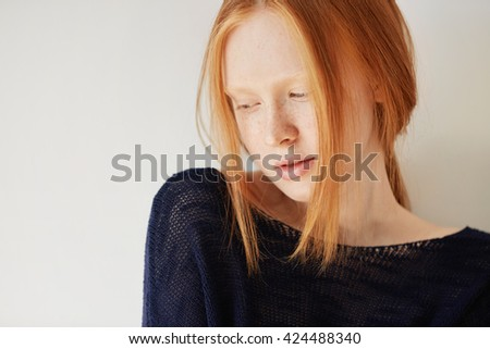 Beautiful female teenage model wearing casual black top looking down with shy and thoughtful expression on her face. Isolated portrait of coy redhead student girl with freckles and no make up  - stock photo