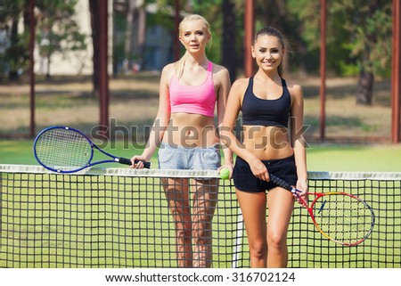 Beautiful female tennis players playing doubles at tennis at the tennis court - stock photo
