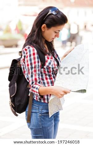 Beautiful female tourist examining map on city streets. - stock photo