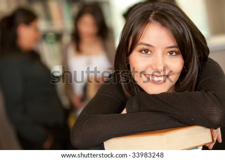 Beautiful female university student at the library - stock photo