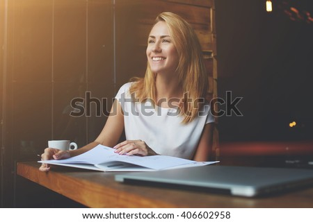 Beautiful female with cute smile looking away while relaxing after work on her laptop computer, charming happy woman enjoying rest and good day while sitting alone in modern coffee shop interior  - stock photo