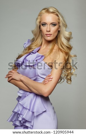 Beautiful female with long blond hair standing with folded hands, over gray background - stock photo