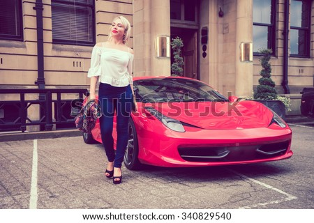 Beautiful female woman with blonde hair, and red lipstick, walking with attitude from a beautiful red coloured sports car. - stock photo