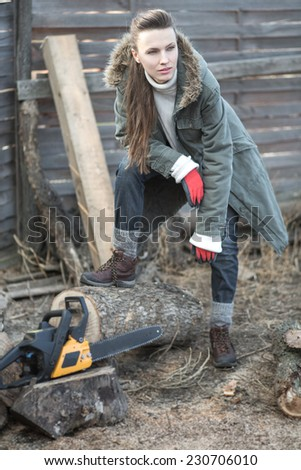 Beautiful female woodworker with chainsaw - stock photo