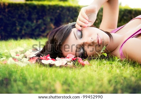Beautiful feminine woman and flower petals in green grass - stock photo