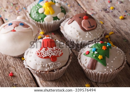 Beautiful festive cupcakes with Christmas decorations close-up on a wooden table. horizontal - stock photo