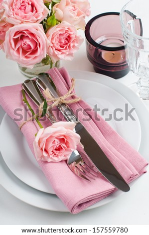 Beautiful festive table setting with roses, candles, shiny new cutlery and napkins on a white tablecloth. - stock photo