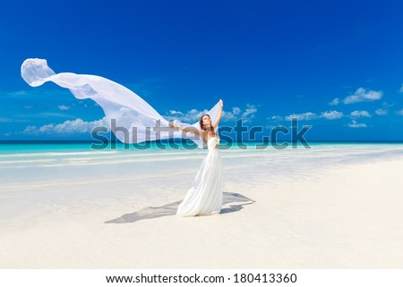 beautiful fiancee in white wedding dress and big long white train, stand on shore sea - stock photo
