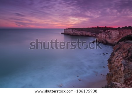 Beautiful fiery sunset on the coast of Portugal. Sea blurred. - stock photo