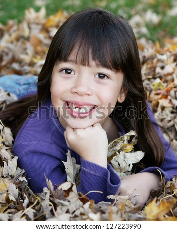 Beautiful Filipino Girl Smiling in a Fall/Autumn setting Showing Missing Top Tooth - stock photo