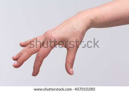 Beautiful fingers of old woman's hand represented over white background. Picture of hand holding something in air.