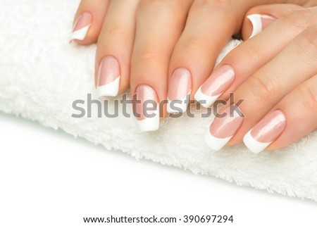 Beautiful fingers with french manicure on the towel. Manicure in a beauty salon.