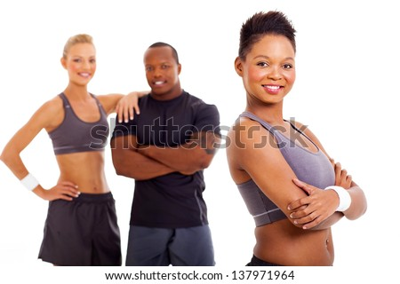 beautiful fit african woman in sportswear with two instructors on background - stock photo