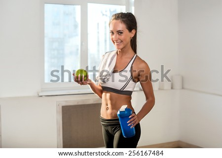 Beautiful fit and slim young athletic sportive woman  in sport outfit is smiling and holding apple and blue shaker after the training - stock photo
