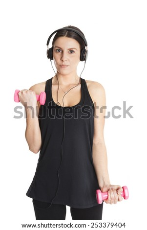 Beautiful fit caucasian lady with headphones trains the biceps with weights. Isolated on white background. - stock photo