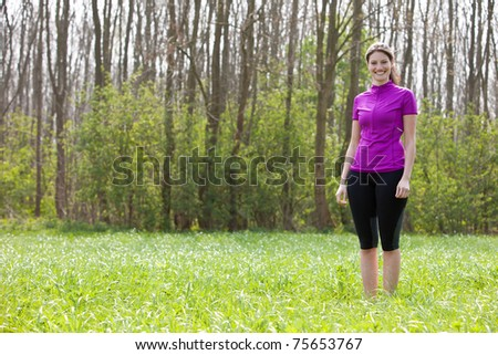 Beautiful fit girl standing in the meadow wearing sportsclothes - stock photo