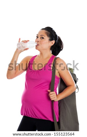 Beautiful fit Hispanic pregnant woman holding yoga mat drinking bottled water isolated on a white background