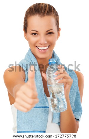 Beautiful fit mixed race female model holding a bottle of water, wearing towel and fitness clothing.Smiling expression, showing thumb up.Success concept.  - stock photo