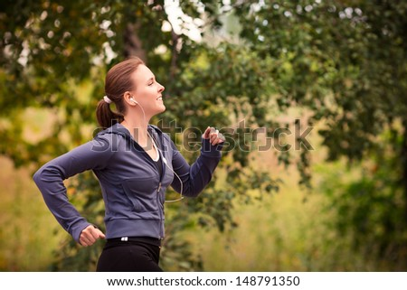 Beautiful fit runner woman jogging in nature outdoor - stock photo