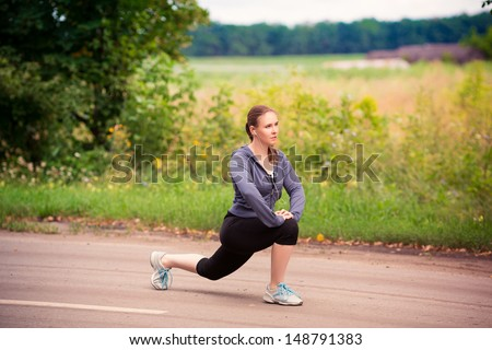 Beautiful fit runner woman stretching after jogging in nature