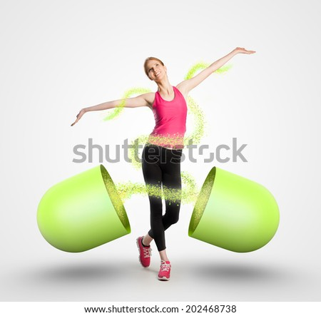 Beautiful fit woman and a giant capsule - stock photo