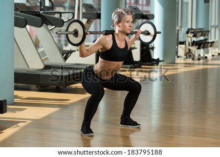 Beautiful Fit Woman Doing Barbell Squats In The Gym