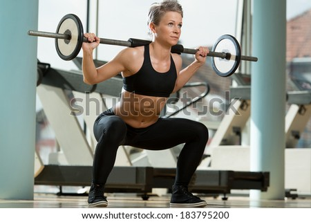 Beautiful Fit Woman Doing Barbell Squats In The Gym - stock photo
