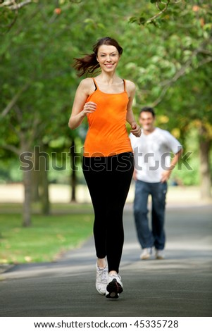 Beautiful fit woman jogging outdoors and smiling - stock photo