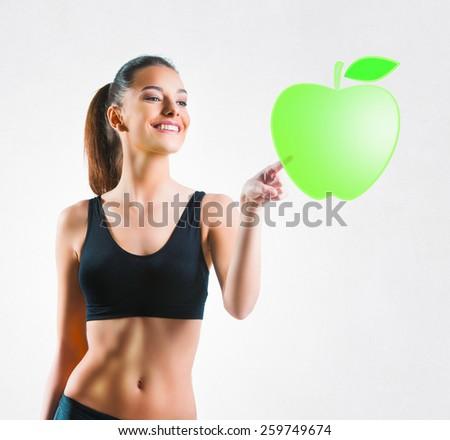 Beautiful fit woman pressing a green apple symbol - stock photo
