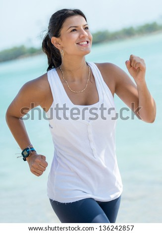 Beautiful fit woman running outdoors by the beach