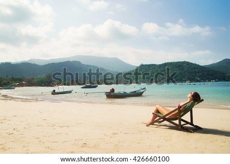 Beautiful, fit woman sunbathing in the deckchair and having a recreation on the beach in Thailand.