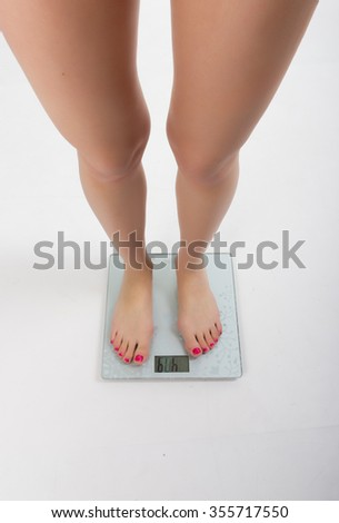 Beautiful fit woman weighed after exercise. fit woman standing on the scales