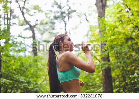 Beautiful fit young woman athlete with long hair and sports top drinks water from the bottle during running in summer autumn forest. Resting at training with trees on background