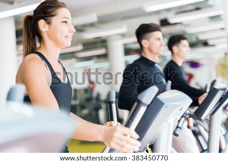Beautiful fit young woman working out on a stepper together with her friends