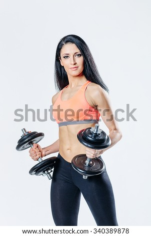 beautiful fitness female posing on studio background with barbells - stock photo