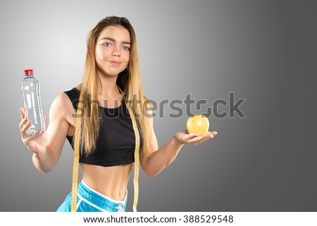 Beautiful fitness girl holding an apple