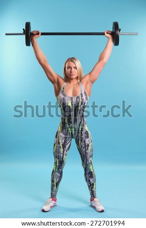 Beautiful fitness girl liftings weights. studio photo