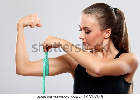 Beautiful fitness girl measure her biceps with a  ruler over grey background - stock photo