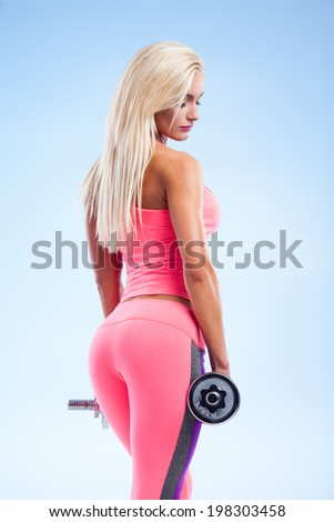 Beautiful fitness model posing with dumbbells on blue background - stock photo