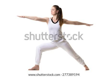 Beautiful fitness model practices yoga or pilates, doing lunge exercise, standing in Warrior II posture, Virabhadrasana 2, side view, studio shot, isolated - stock photo