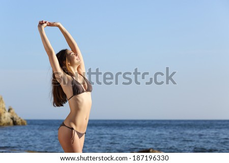 Beautiful fitness woman body posing wearing a swimsuit on the beach with the sea and the horizon in the background - stock photo