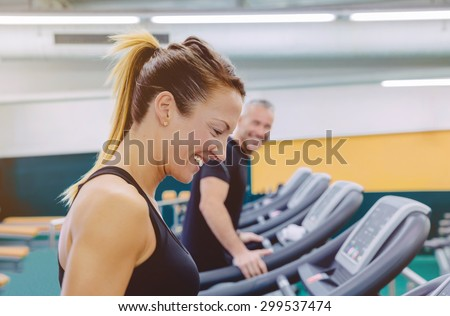 Beautiful fitness woman laughing with friend in a treadmill training on fitness center - stock photo