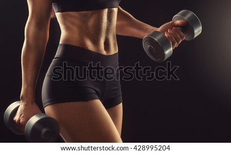 Beautiful fitness woman lifting dumbbells . Fitness sporty woman showing her well trained body . A beautiful girl's body with rippling muscles from strength training . - stock photo