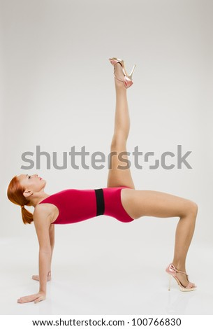 Beautiful fitness woman performing handstand with one leg up wearing high heels - stock photo