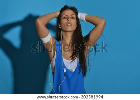 beautiful fitness woman posing against the blue background - stock photo