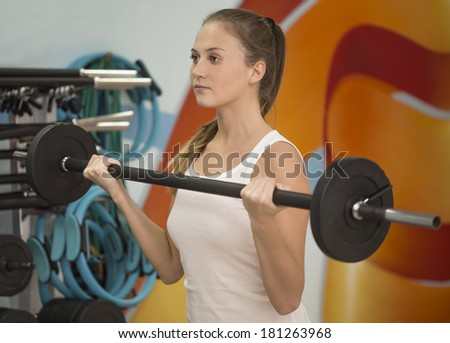 Beautiful fitness woman practicing with dumbbell