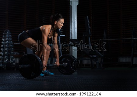 Beautiful Fitness Woman preparing to lift some heavy weights.  - stock photo
