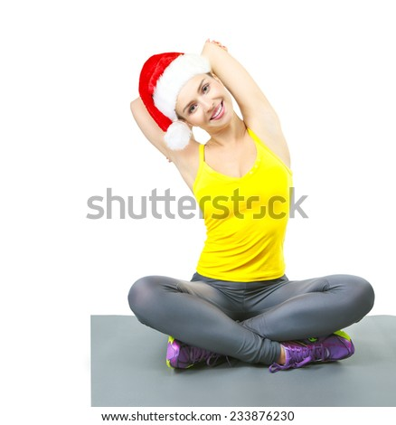 Beautiful fitness woman smiling with Santa Hat, doing exercises on yoga mat, isolated on white background. Caucasian female fitness model, Christmas.  - stock photo